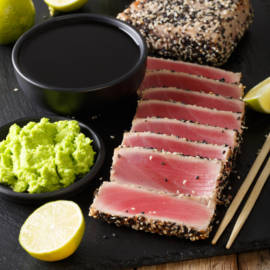 Healthy food: tuna steak in sesame and soy sauce, wasabi, lime closeup on the table. vertical